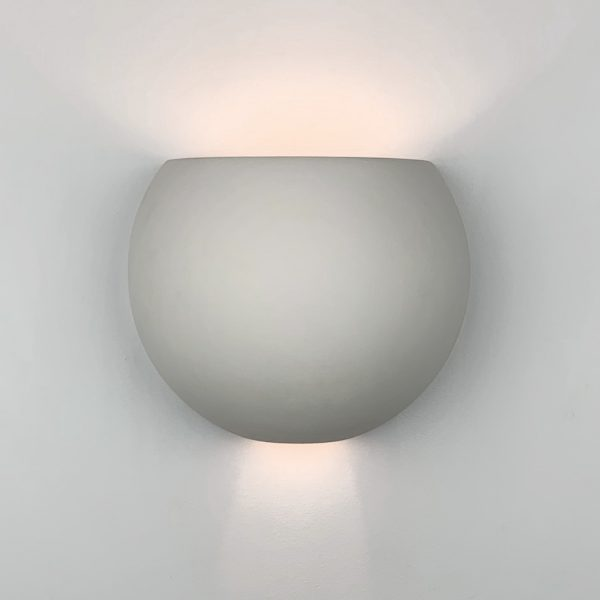 Curacao Sconce is a modern sphere-shaped wall sconce. It features a cutout at the bottom and an open top.